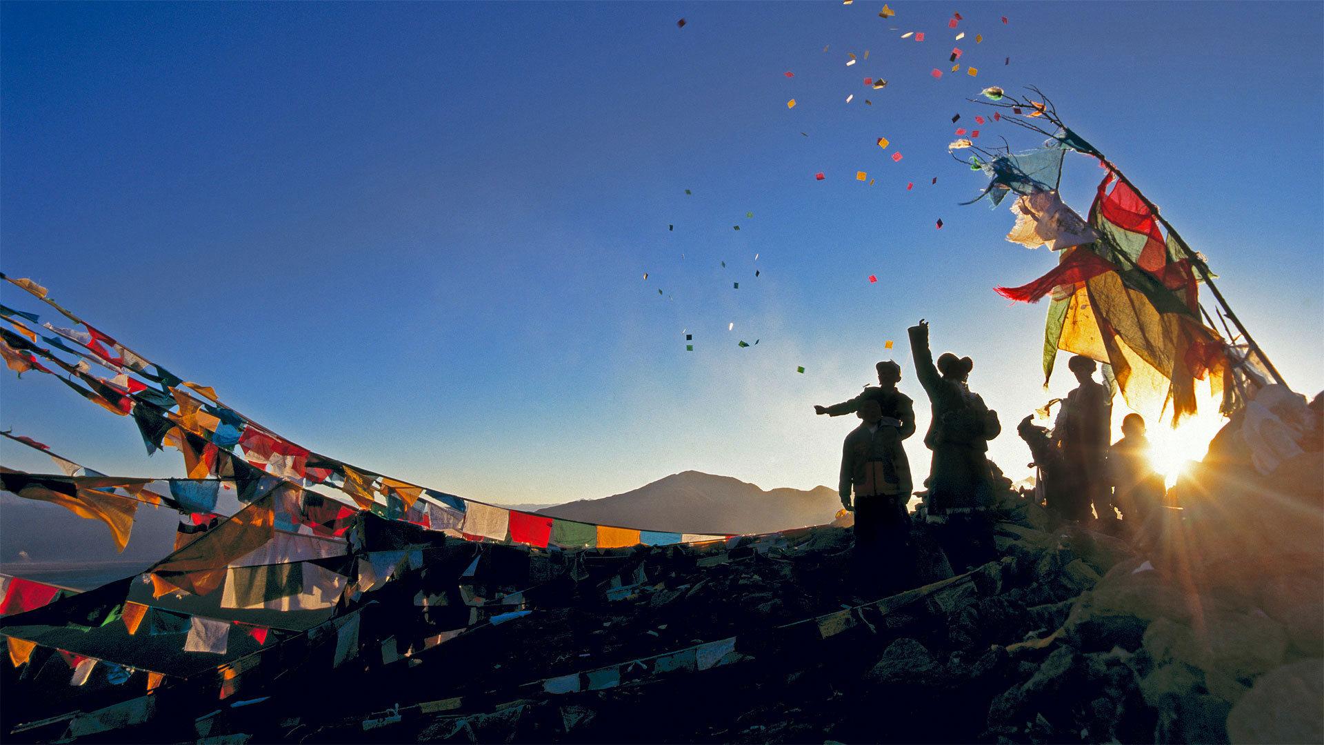 朝圣者将风马旗扔向甘登寺上方的空中为新年祈福风马旗