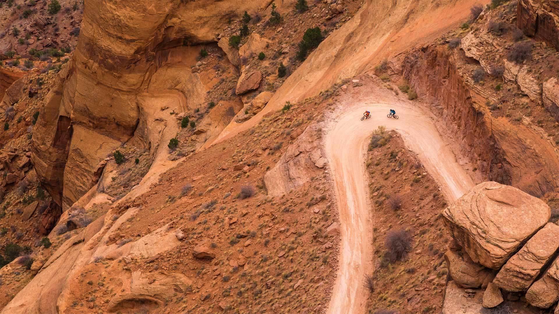 两名山地车骑手在白缘公路上沿着谢福小道的转弯处骑行峡谷地国家公园