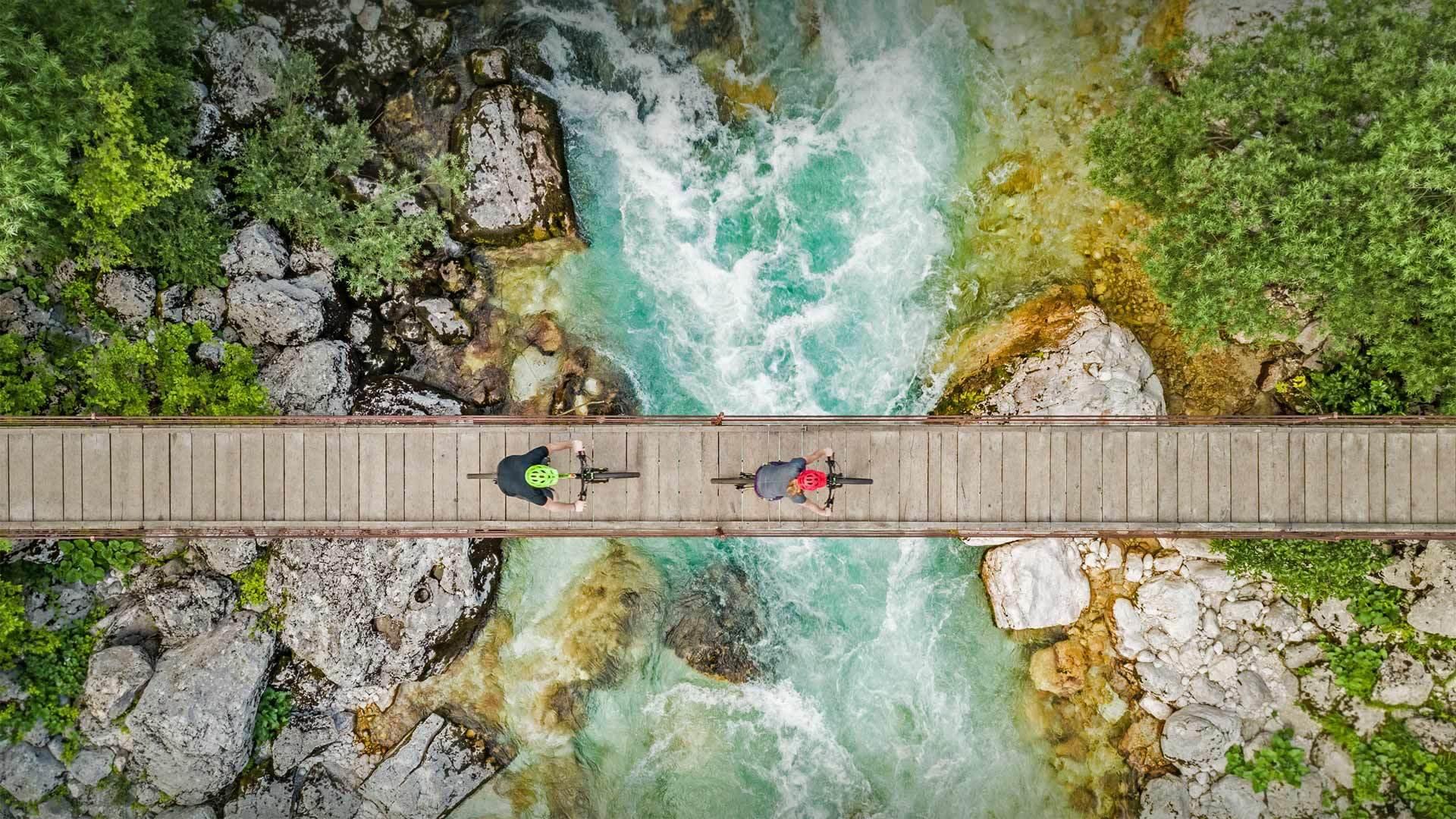 斯洛文尼亚索奇河上的木制吊桥上骑自行车的人的鸟瞰图 斯洛文尼亚索奇河